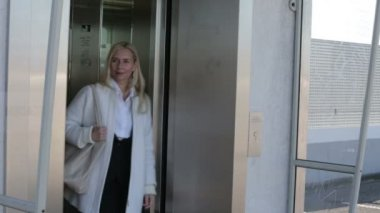 Blond woman walking out of an elevator and looking for someone — Stock Video