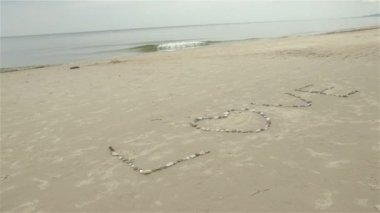 Word love written with pebbles on the sand of a baltic beach — Stock Video