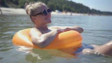 Pretty girl floats on a lifebuoy ring in the sea, somewhere in Poland. — Stock Video