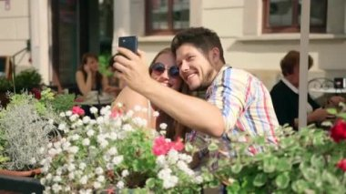 Young couple taking a selfie together on the cafe terrace on sunny day — Stock Video