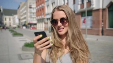 Young happy woman texting on mobile phone during sunny day in a city. — Stock Video