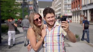 Attractive couple taking self-portrait with smartphone in a city street — Stock Video