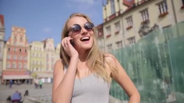 Cheerful woman in sunglasses talking on mobile phone in the city. — Stock Video