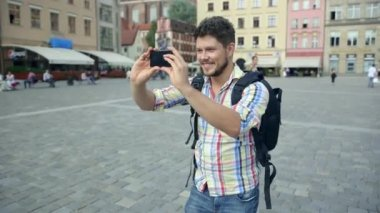 Young casual man with beard taking picture with camera phone outdoors. — Stock Video