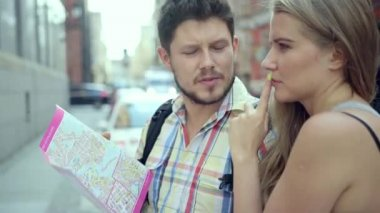 Young attractive couple with a city map trying to find a right direction. — Stock Video