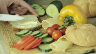 Making sandwich with cheese, tomato, cucumber on a wooden board — Stock Video