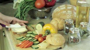 Fare il sandwich con formaggio, pomodoro, cetriolo su una tavola di legno — Video Stock