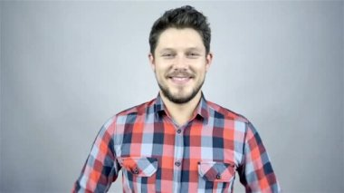 Young smiling man in a red checkered shirt on grey background — Stock Video