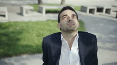 Young businessperson sitting on a bench and relaxing in a park — Stock Video