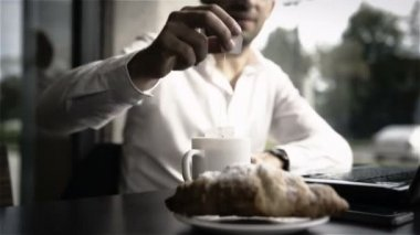 Business man making tea while working at desk with breakfast croissant — Stock Video