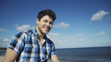 Handsome young man in casual checkered shirt against bright beach background — Stock Video