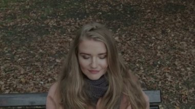 Pretty  woman sitting on a bench in a park waiting for someone. Closeup. — Stock Video