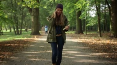 Attractive young woman talking on mobile phone in beautiful autumn park. — Stock Video