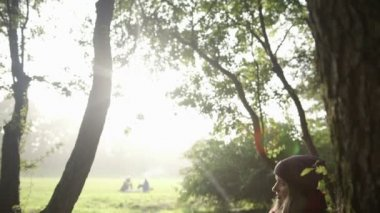 Women resting and talking by smartphone under the tree in park. — Vídeo de stock