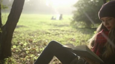 Portrait of beautiful young caucasian girl reading a book in the autumn park. — Stock Video
