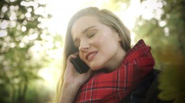 Happy young woman talking on mobile phone in autumn park. — Stock Video