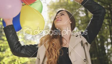 Cheerful brunette girl with colorful balloons smiling in autumn park. — Stock Video