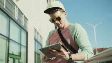 Young stylish teenager using tablet in a city street during sunny day. — Stock Video