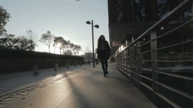 Silhouette of young girl walking joyfully in the city streets, slow motion. — Stock Video