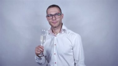 Young handsome man in white shirt celebrate with champagne over grey background. — Stock Video