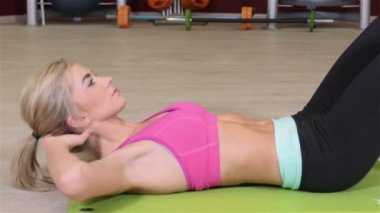 Beautiful sporty woman doing crunches on the floor in a fitness center. — Stock Video