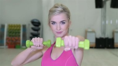 Fitness woman working out with dumbbells in a gym. — Stock Video