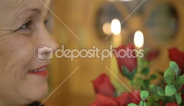 Mature woman holding large bouquet of red roses and smiling. — Stock Video