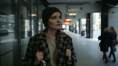Pensive young fashion woman with backpack walking in the city, steadicam shot — Stock Video