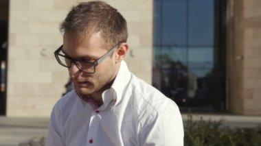 Glückliche junge Geschäftsmann am Telefon sitzt vor seinem Büro. — Stockvideo