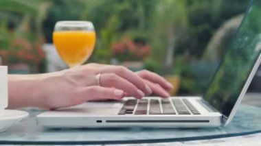 Close up of woman's hands typing on a laptop computer outdoors. — Stock Video