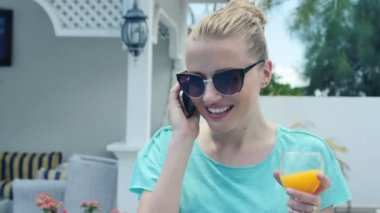 Young smilling woman talking on a mobile phone in the garden. — Stock Video