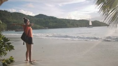 Young woman wearing sunglasses relaxing on a tropical beach.Side portrait of a young woman breathing fresh air, standing on a beach. — Stock Video