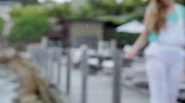 Jolie jeune femme en combinaison blanche marche sur la jetée en bois en été. — Vidéo