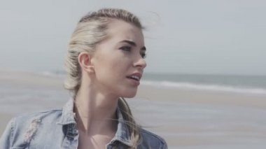 Happy young woman in denim jacket having fun time on lonely beach. — Stock Video