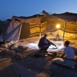 People sits by the light at night in desert — Stock Photo #60927867