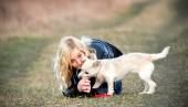 Blond girl playing with her puppy — Stockfoto