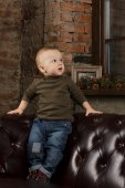 Cute toddler on a leather sofa — Stock Photo