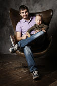 Father and son on a leather arm-chair — Stock Photo