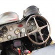 Dashboard and steering wheel in interior of italian classic sport car isolated on white background — Stock Photo #76907429