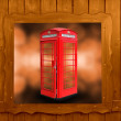 Classic British red phone booth in London UK, wooden window — Stock Photo #58018905