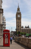 LONDON - JULY 25: London traffic with red phone booth  and Big Ben on July 25, 2013 in London, England — Stock Photo
