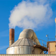 Smoking chimneys of a factory against a blue sky — Stock Photo #65726807