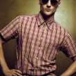 Closeup portrait of a young gorgeous fashion man wearing trendy sunglasses & posing over golden background. Male beauty & eyewear concept. Hipster style — Stock Photo #55921055