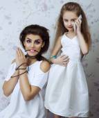 Portrait of Two beautiful sisters (girls) at studio.  Perfect skin and make up. The concept of the problem of the modern world, dependence on gadgets. — Stock Photo