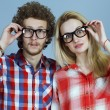 Portrait of gorgeous blond fashion man and woman (couple) in casual shirt  wearing trendy eyeglasses posing over blue background. Perfect skin and hairdo. Vogue style. Close up.  Eyewear concept. — Stock Photo #65681865