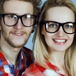 Portrait of gorgeous blond fashion man and woman (couple) in casual shirt  wearing trendy eyeglasses posing over blue background. Perfect skin and hairdo. Close up. Studio shot. Eyewear concept. — Stock Photo #65681867