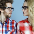 Portrait of gorgeous blond fashion man and woman (couple) in casual shirt  wearing trendy eyeglasses posing over blue background. Perfect skin and hairdo. Vogue style. Close up.  Eyewear concept — Stock Photo #65681869