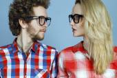 Portrait of gorgeous blond fashion man and woman (couple) in casual shirt  wearing trendy eyeglasses posing over blue background. Perfect skin and hairdo. Vogue style. Close up.  Eyewear concept — Stock Photo