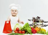 Little Chef boy preparing healthy food and looking and smiling in camera over white background. the concept of vegetarianism — Stock Photo