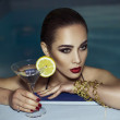 Beautiful woman enjoying near the pool her vacation with a glasses of martini. beautiful and perfect makeup, clean skin, jewelry on the body. — Stock Photo #77403532
